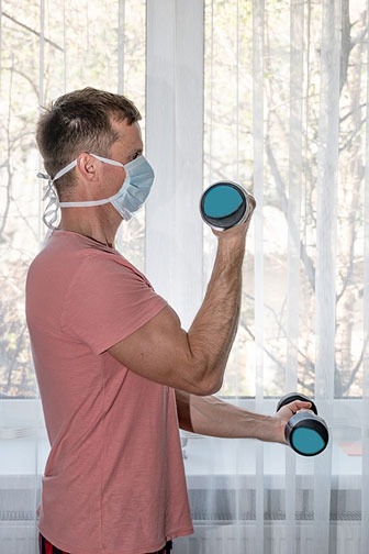 man lifting dumbbells at home while wearing a protective mask